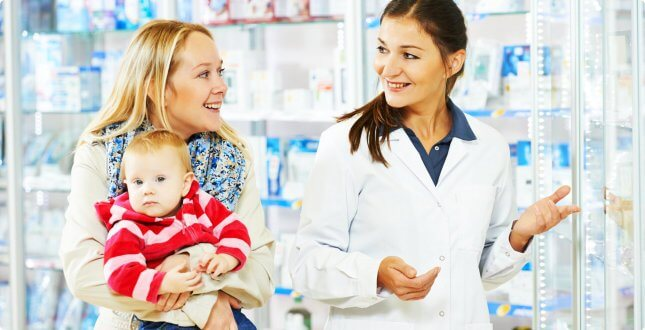 The pharmacist is talking to her costumer